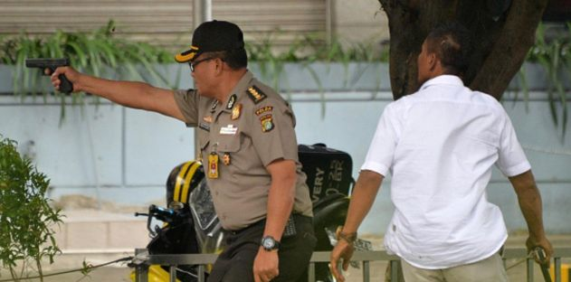 An Indonesian policeman fires his handgun towards suspects outside a cafe after a series of blasts hit the Indonesia capital Jakarta on January 14, 2016. At least four people have been killed, one police officer and three civilians, after blasts on January 14 hit the Indonesian capital Jakarta, police said.    AFP PHOTO / Bay ISMOYO / AFP / BAY ISMOYO        (Photo credit should read BAY ISMOYO/AFP/Getty Images)